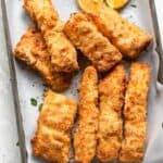 Breaded fish after air fried on a tray with lemon wedges
