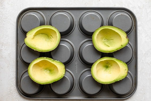 Placing avocados inside muffin tins for baking