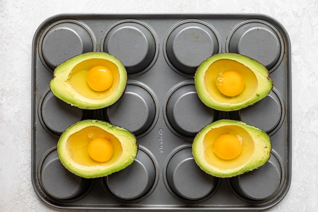 Cracked eggs inside 4 avocado halves before baking