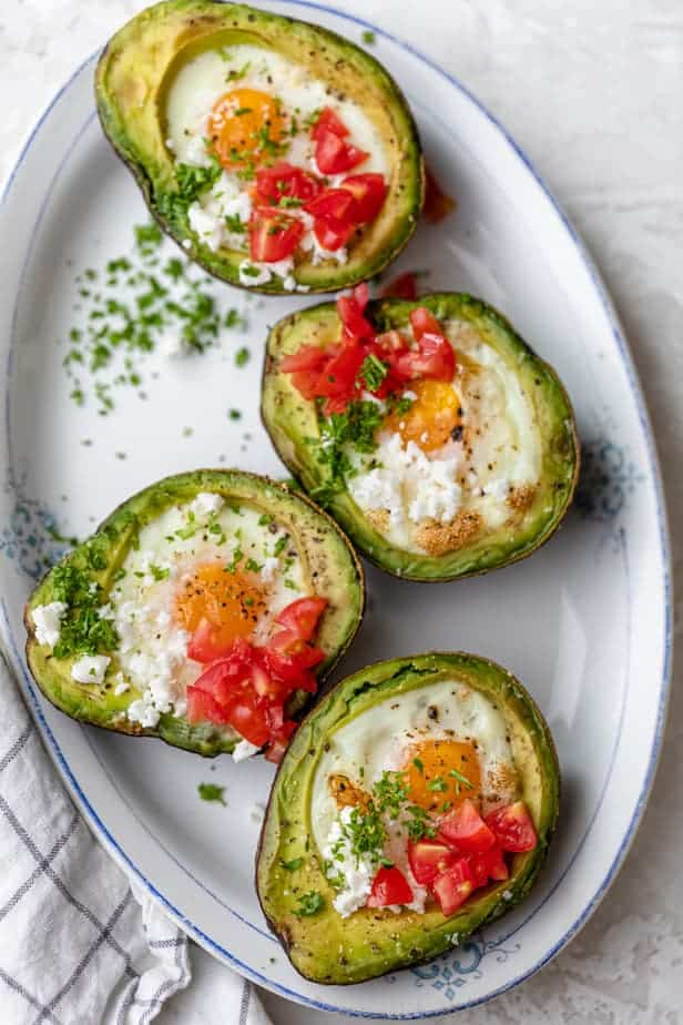 Bakes eggs in avocado garnished with tomatoes, feta cheese and parsley