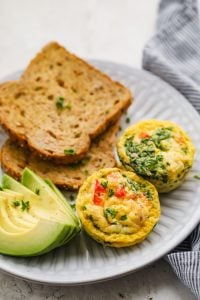 Breakfast egg cups served on a plate with toast and avocados