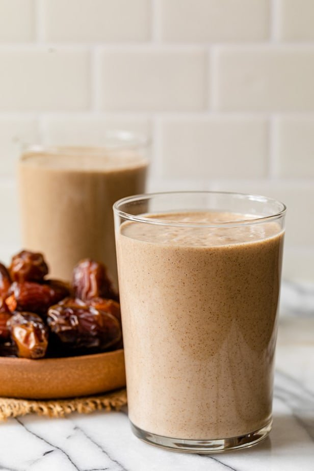 A date shake in a glass in front of a plate of dates