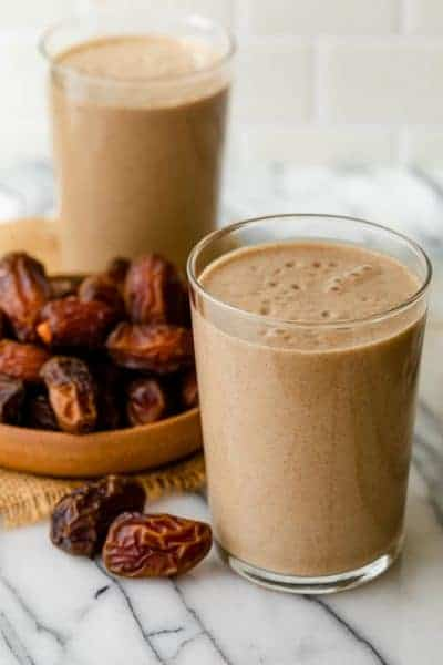 2 cups of date shakes with bowl of dates next to them