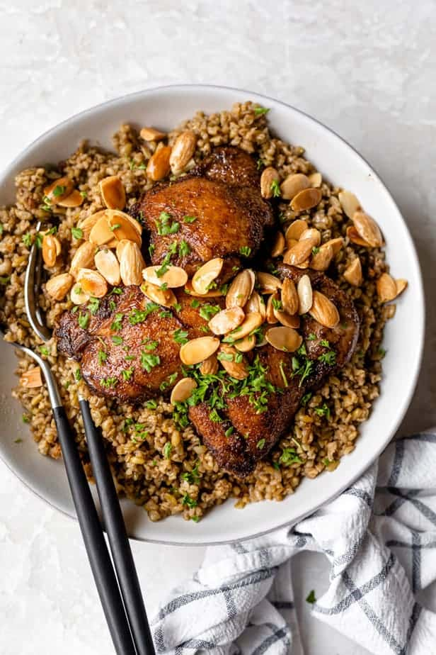 Freekeh with chicken in a large white serving bowl