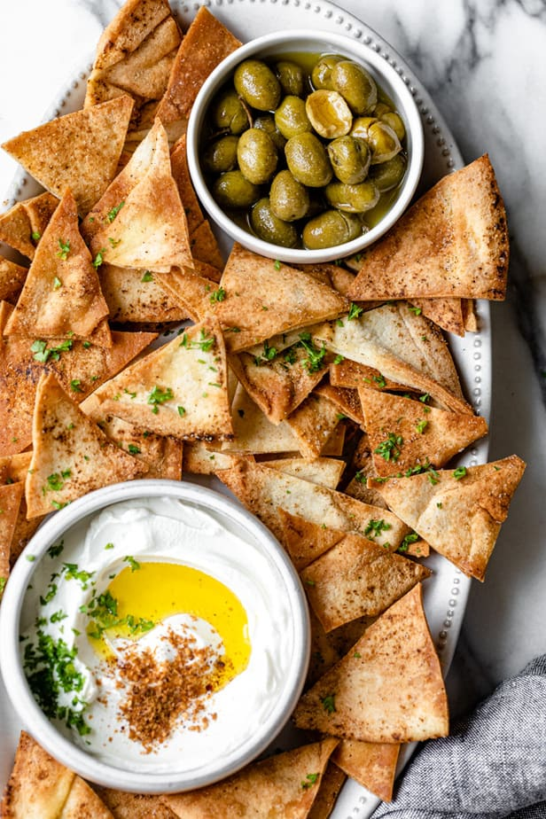 Pita chips on a platter served with yogurt cheese (labneh) and olives