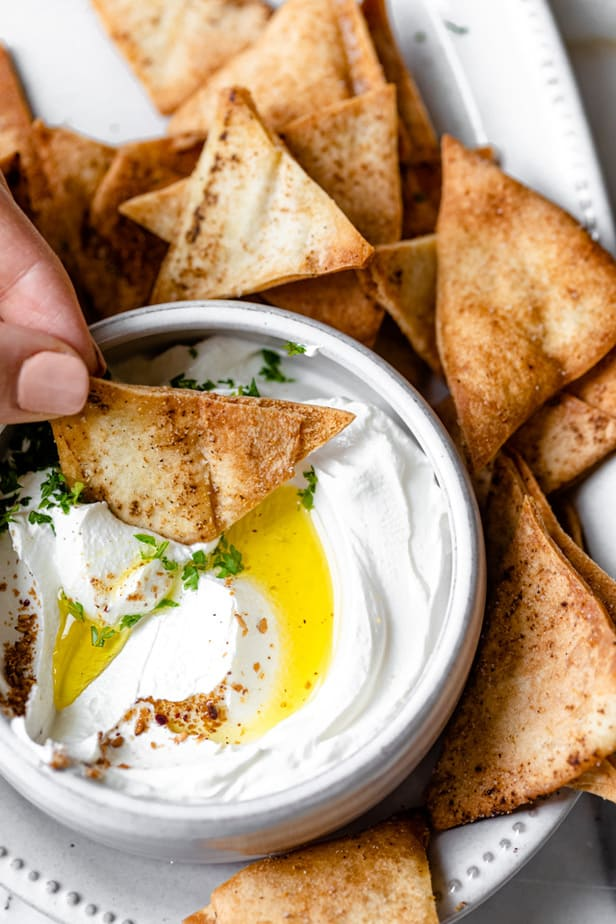 Dipping the pita chip into labneh