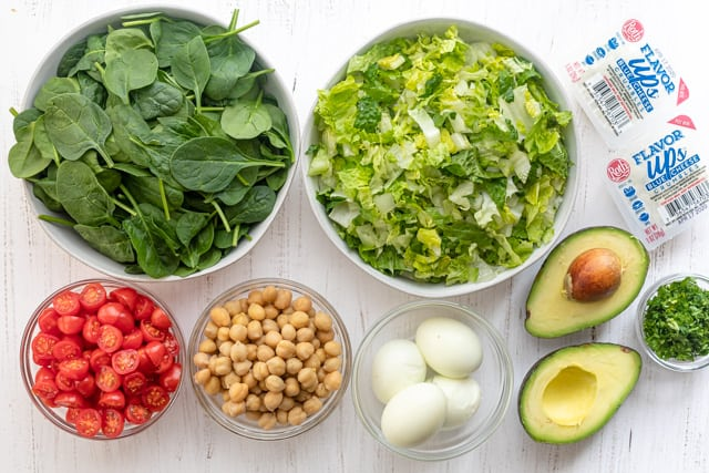 Ingredients to make the vegetarian cobb salad: spinach, lettuce, tomatoes, chickpeas, eggs, avocado, parsley and blue cheese