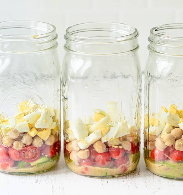 Adding the smaller items at the bottom of the jars
