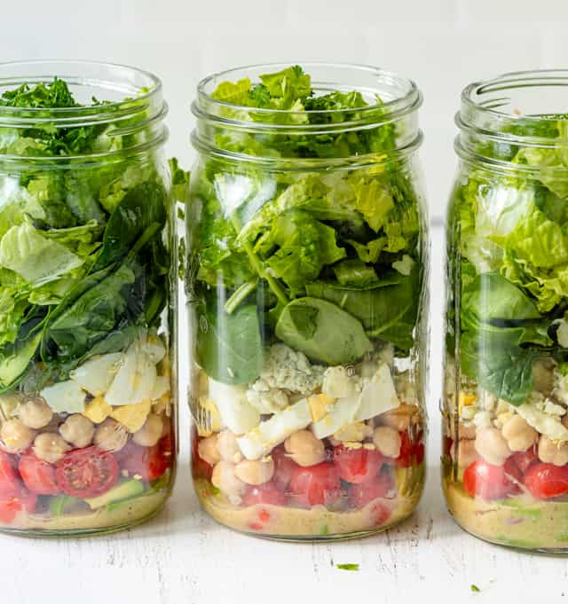 Filling in the jars with the remaining ingredients for the vegetarian cobb salad