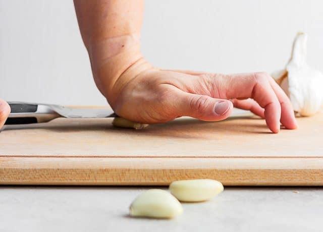 knife crushing garlic clove