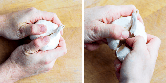 hands pulling off cloves from a garlic bulb