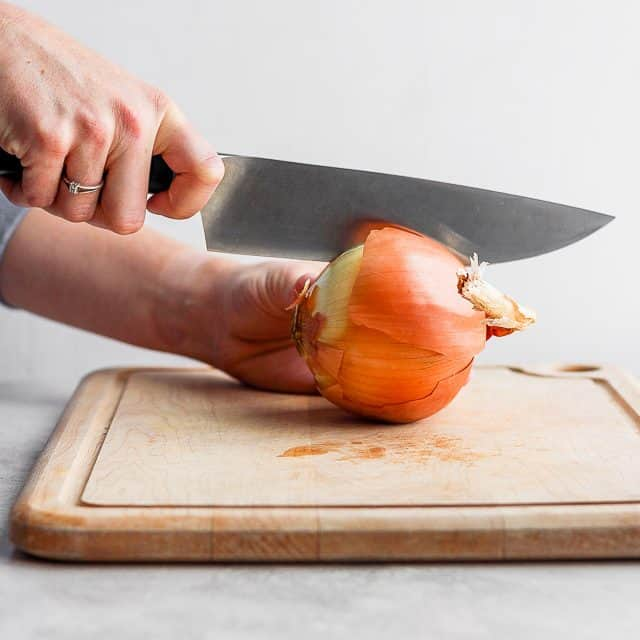 Large chef's knife cutting into onion on cutting board
