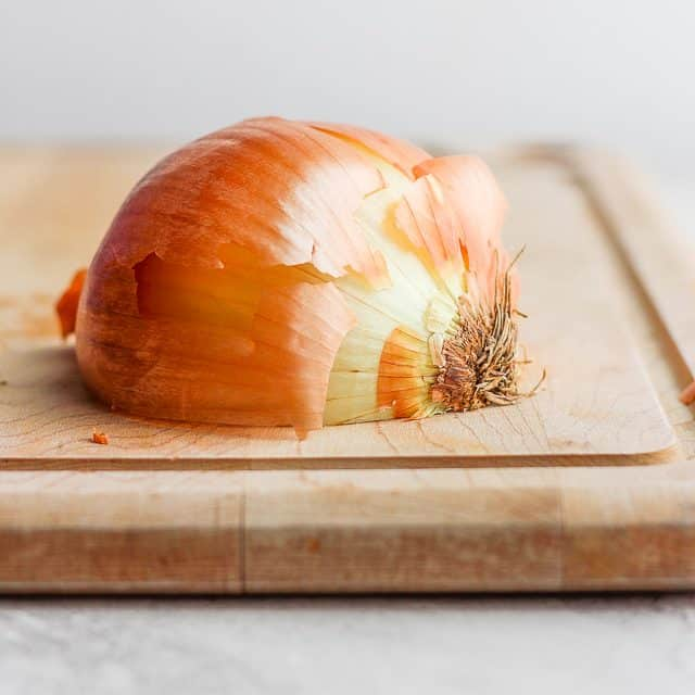 Laying half the onion on cutting boards cut size down