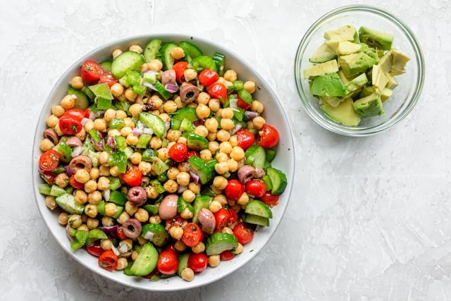 The chickpea salad ingredients tossed with the dressing in a white bowl