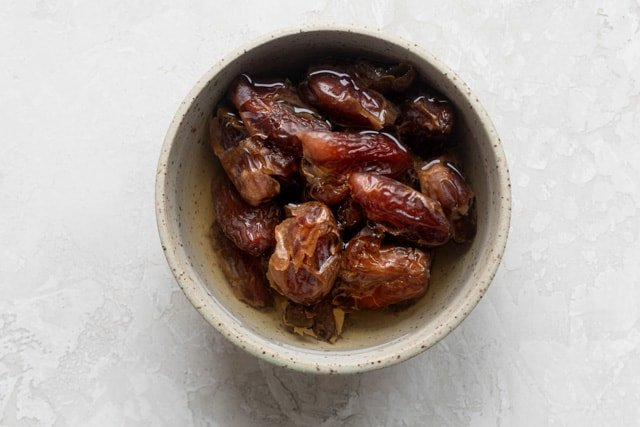 Soaking dates in warm water to soften them