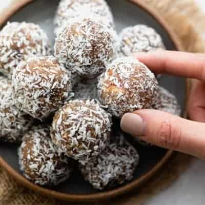 Hand grabbing one of the coconut date balls from shallow bowl