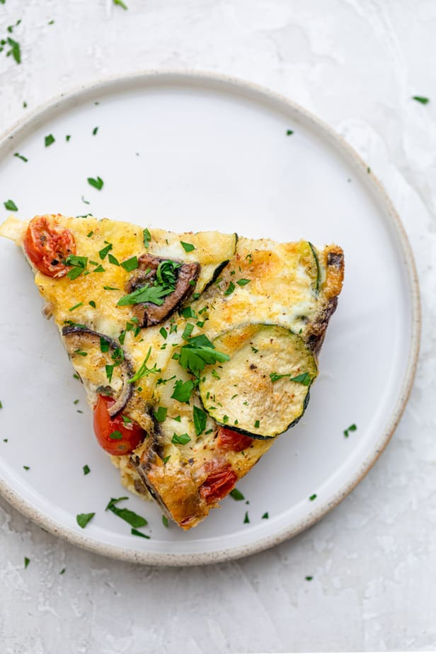 A slice of crustless quiche on a white plate