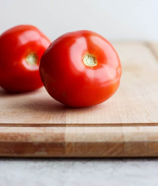 Two vine ripe tomatoes on a cutting board