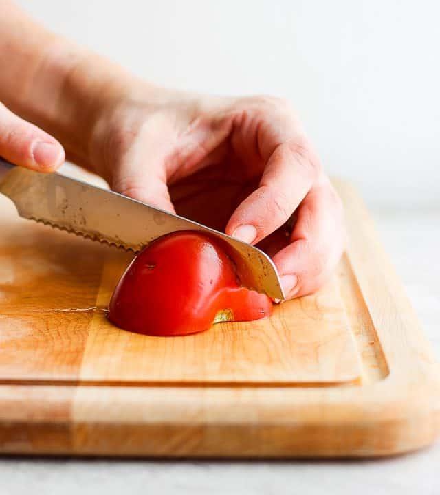 Knife cutting through a tomato half