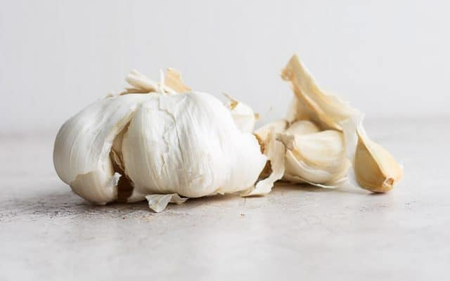 side shot of garlic and cloves