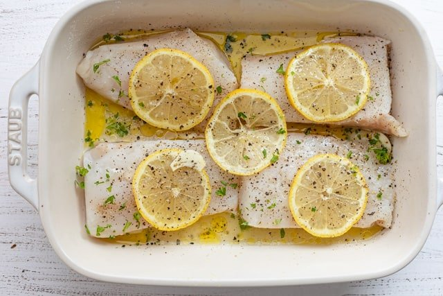 The fish topped with sliced lemon ready to cook
