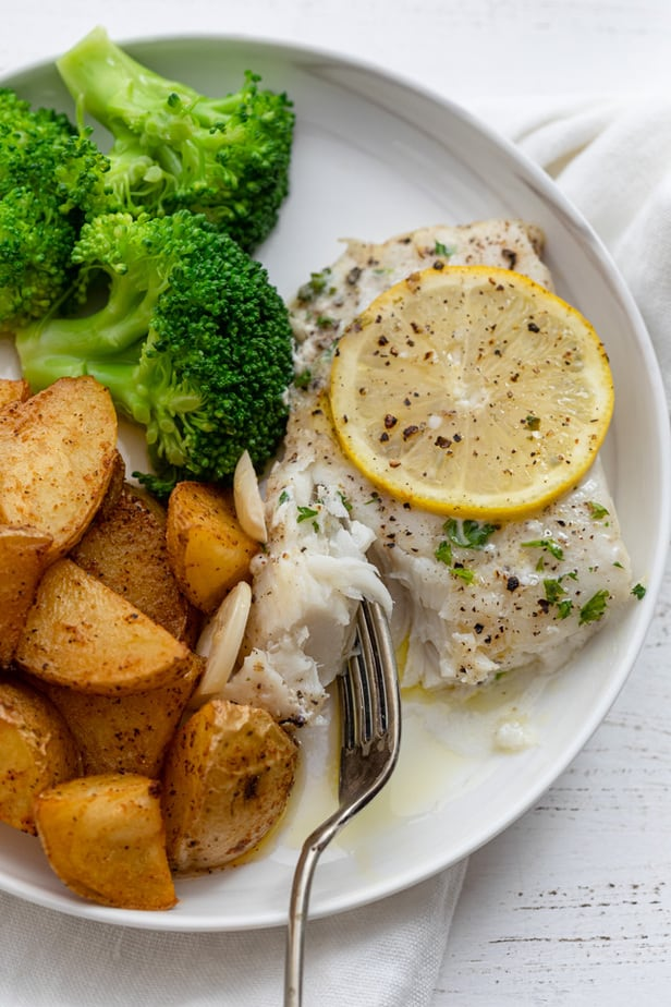Baked cod served with potatoes and broccoli on a white plate