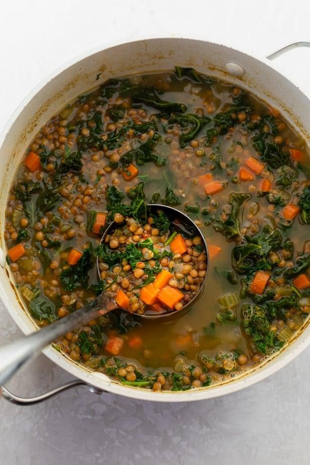 bowl of lentil kale soup with a ladle