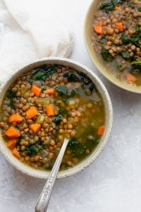 Two bowls of lentil kale soup with a spoon inside one bowl