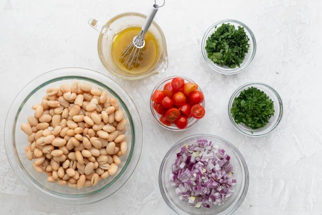 The white bean salad ingredients in glass bowls