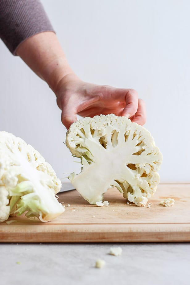 hand holding half a cauliflower