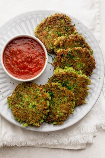 Broccoli fritters on a white plate with a dipping sauce