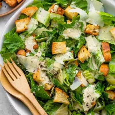 Caesar salad served in a white bowl with wooden salad servers