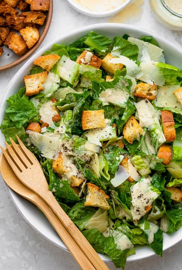 Caesar salad in a white bowl with wooden salad servers