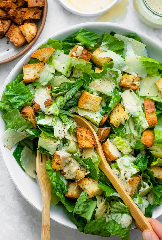 Serving the Caesar salad with serving spoons