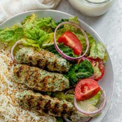 Chicken kafta on a plate with rice and salad along with garlic sauce on the side