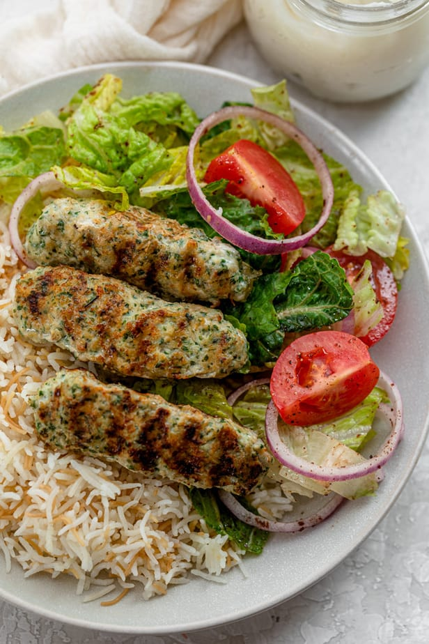 Close up of the chicken kaftas served with a side salad and Lebanese rice
