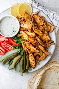 Chicken shawarma on a white plate with sliced vegetables and pickles