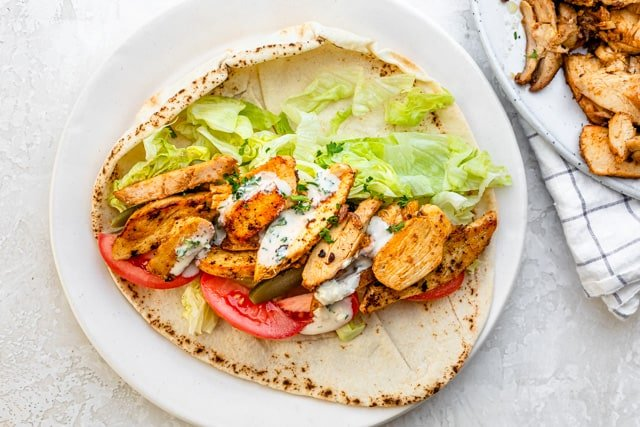 Chicken shawarma served in pita with fresh vegetables and sauce