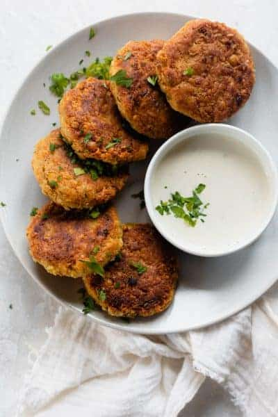 Chickpea fritters on a white plate with a dip