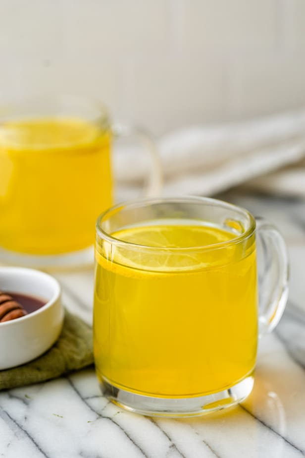 A glass of Ginger Turmeric Tea with a slice of lemon