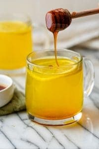 Honey being drizzled into Ginger Turmeric Tea