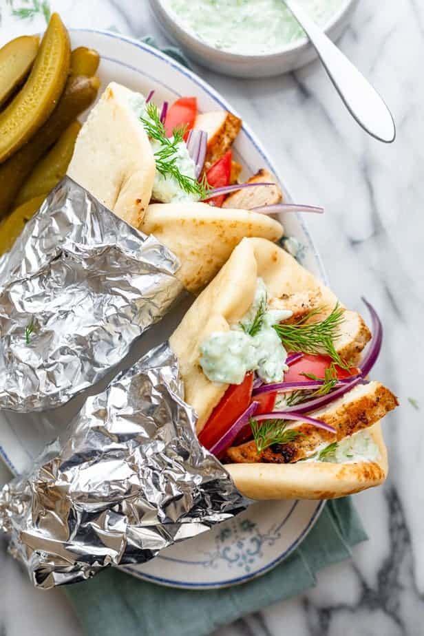 Two chicken gyros on a plate wrapped in foil
