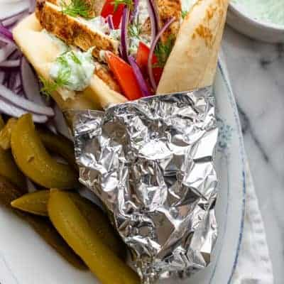 Chicken gyro after grilling served with pickles and tzatziki