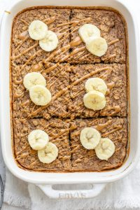 Banana baked oatmeal drizzled with peanut butter and top with banana slices