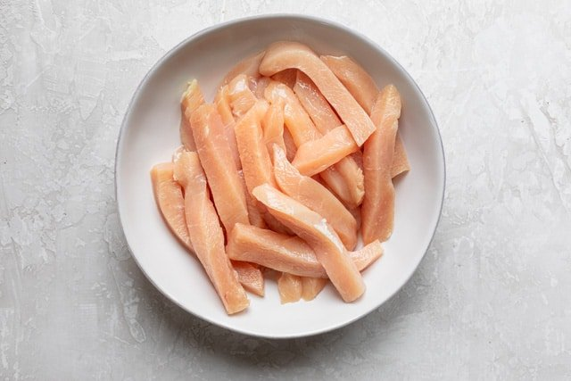 Strips of chicken breast in a bowl