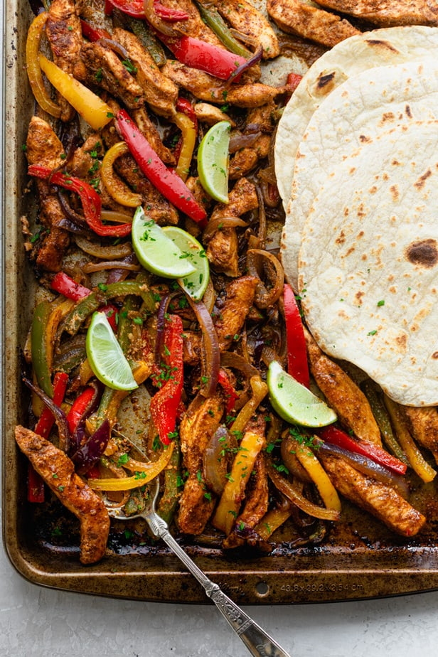 Sheet pan chicken fajitas garnished with lime wedges