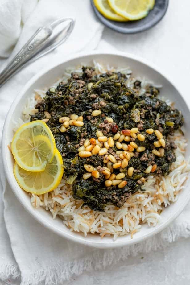Lebanese Spinach Stew (Sabanekh wu riz) served with pine nuts and lemon slices