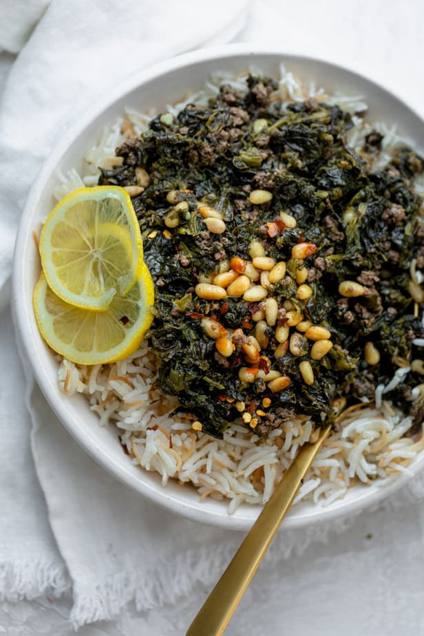 Lebanese spinach stew (sabanekh) served over rice with lemon slices and pine nuts