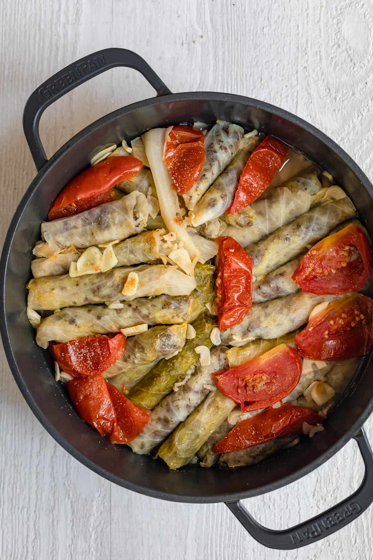 Showing the alternating layers of stuffed cabbage in a large pot with garlic, tomato slices and green peppers