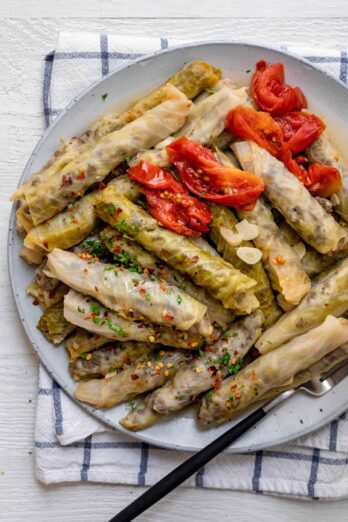 Plate of stuffed cabbage rolls - lebanese style served with tomato slices